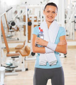 Beautyful smiling standing sportswoman with bottle of water — Stock Photo