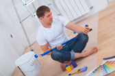 Painter sitting on floor with crossed legs — Stock Photo