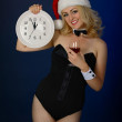 Girl in the hat of Santa Claus with a clock — Stock Photo