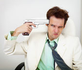 Tattered businessman in white suit with gun — Stock Photo