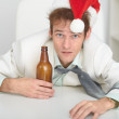 Young man in Christmas hat at office with a beer — Stock Photo #2316576