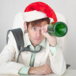 Amusing guy in Christmas cap with bottle in a ha — Stock Photo #2318337