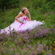 Stock Photo: Young beautiful bride sitting at a forest glade