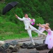 Stock Photo: Groom with umbrella and bride - wedding joke