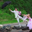 Stock Photo: Groom with umbrelland bride - wedding joke