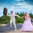Groom with suitcase seeks for a honeymoon — Stock Photo