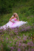 Young beautiful bride sitting at a forest glade — Stock Photo