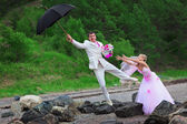 Groom with umbrella and bride - wedding joke — Stock Photo