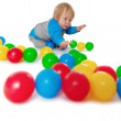 Comical child playing with colored plastic balls — Stock Photo