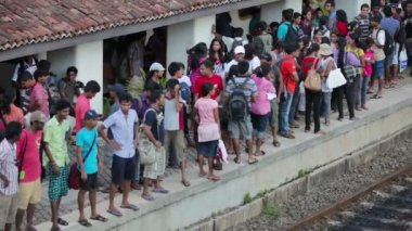 BENTOTA, SRI LANKA - May 02: Passengers wait for a train on the station on May 02, 2013 in Bentota, Sri Lanka. Sri Lanka Railways a linking Colombo and many population centres and destinations. — Stok video
