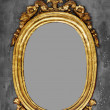 Old-fashioned gilt frame for a mirror on a concrete wall — Stock Photo