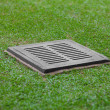 Stock Photo: Sewer grate on the lawn - drainage for heavy rain