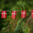 Small Danish flags decorate tropical palms in Thailand — Stock Photo
