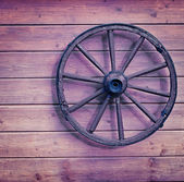 Vintage wooden wheel on wall — Stock Photo