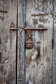 Rusty padlock on an old wooden door of the house — Foto Stock