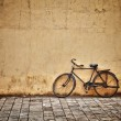 Old vintage bicycle near the wall — Stock Photo