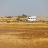 Bus carries tourists to the rocky desert. India — Stock Photo