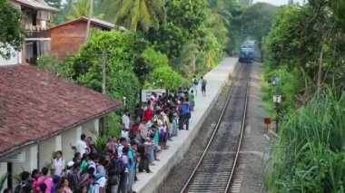 BENTOTA, SRI LANKA - APR 28: Train arrive to station with waiting people on Apr 28, 2013 in Bentota, Sri Lanka. Trains are becoming more popular transport due to railway improvement by government. — Stok video