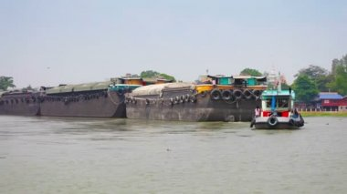 AYUTTHAYA, THAILAND - APR 1: Big metal the barge is in tow on wide Chao Phraya river on Apr 11, 2013 in Ayutthaya, Thailand. Rivers use extensively as transport channel in Asian countries. — Stok video