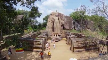 KEKIRAWA, SRI LANKA - APR 16: Pilgrims pray near Avukana Buddha statue on Apr 16, 2013 in Avukana, Sri Lanka. It is 40 feet (12 m) high standing statue carved out of granite rock in the 5th century. — Stok video