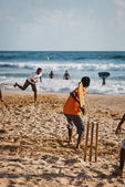 BENTOTA, SRI LANKA - APR 28: Teenagers play cricket with bat and — Stok fotoğraf