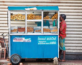 BENTOTA, SRI LANKA - APR 27: Man buys food in small portable str — Stok fotoğraf