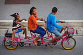 Three childred on tandem bicycle on a road — Stok fotoğraf