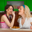 Two young girls funny testing the cookies in the kitchen — Stock Photo