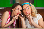 Two funny girls get a phone call in the kitchen — Stock Photo