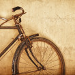 Old-fashioned rusty bicycle near the wall — Stock Photo #34699985