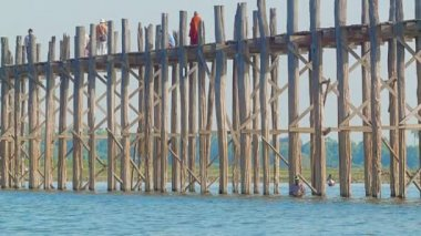 MANDALAY, MYANMAR - 13 JAN 2014: U Bein Bridge across the Taungthaman Lake. The 1.2 km  bridge was built around 1850 and is the oldest and longest teakwood bridge in the world — Stok video