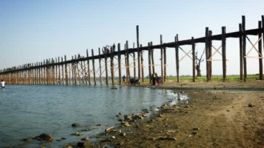 MANDALAY, MYANMAR - 13 JAN 2014: U-Bein Bridge across the Taungthaman Lake. The 1.2 km  bridge was built around 1850 and is the oldest and longest teakwood bridge in the world — Stok video