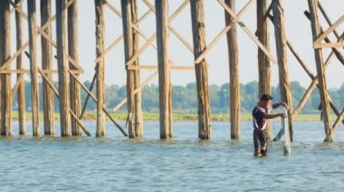 MANDALAY, MYANMAR - 13 JAN 2014: Fisherman fishing near U Bein Bridge on the Taungthaman Lake. Bridge was built around 1850 and is the oldest and longest teakwood bridge in the world — Stock Video