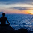 Young man practicing yoga on ocean shore — Stock Photo #41777381