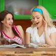 Funny girlfriends browsing magazines on kitchen — Stock Photo