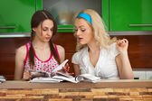 Two girls leaf through  magazines on kitchen — Stock Photo