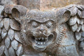 Muzzle fantastic beast on the wall of an old Indonesian temple — Stock Photo