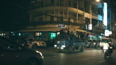 PHNOM PENH, CAMBODIA - 29 DEC 2013: Night traffic on city streets. Groups of people go on the streets in the backs of the trucks — Stock Video