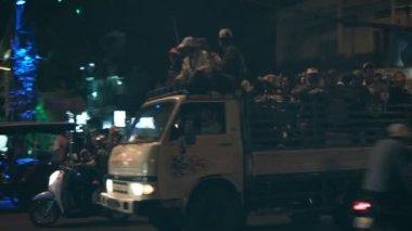 PHNOM PENH, CAMBODIA - 29 DEC 2013: Night city streets. People in the backs of the trucks — Stock Video