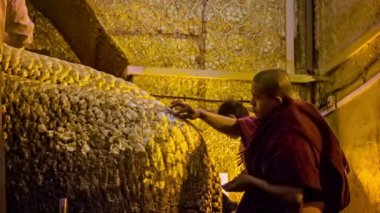 MANDALAY, MYANMAR - 13 JAN 2014: People put golden leaves on Mandalay Maha Myat Muni Buddha Image in Mahamuni Buddha Temple. It is major pilgrimage site in Mandalay and Burma. — Stock Video