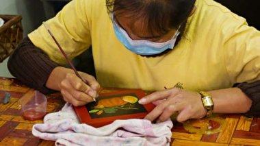 Siem reap, cambodia - circa dec 2013: kvinna målar en bild i verkstaden. kambodja, siem reap — Stockvideo