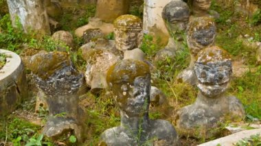 VIENTIANE, LAOS - 13 DEC 2013: Stone statues stick up from ground  in Buddha park also known as Xieng Khuan sculpture park — Stock Video
