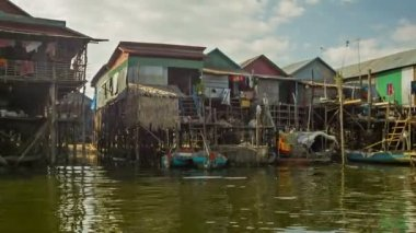 SIEM REAP, CAMBODIA - 21 DEC 2013: Village on high wooden poles on Tonle Sap lake. Tonle Sap is the largest freshwater lake in Southeast Asia. — Stock Video