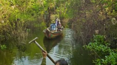SIEM REAP, CAMBODIA - 21 DEC 2013: Small boats rowed by one oar beetween trees and bushes on Tonle Sap lake. Tonle Sap is the largest freshwater lake in Southeast Asia. — Stock Video