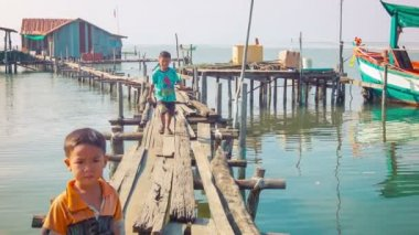 SIHANOUKVILLE, CAMBODIA - CIRCA DEC 2013: Local fishermen kids running on the walkways near the water — Stock Video
