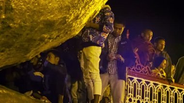 MON STATE, MYANMAR - 04 JAN 2014: Only male people glued small pieces of gold to the sacred rock - Kyaiktiyo Pagoda — Stock Video