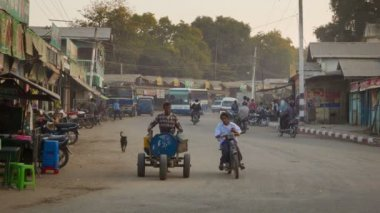 BAGAN, MYANMAR - 11 JAN 2014: Common Asian Burmese dusty road with transport traffic on a street with cars water carriage cart and motorbikes. — Stock Video