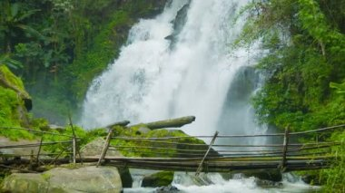 Video 1080p - Tourists cross the river on a background of a waterfall. Doi Inthanon National park, Thailand — Stock Video