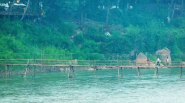Video 1080p - People cross the river with the help of a bamboo footbridge. Luang Prabang, Laos — Stock Video