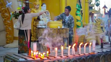 YANGON, MYANMAR - 03 JAN 2014: Parishioners watered Buddha statues. Traditional ritual of bringing benefit — Stock Video